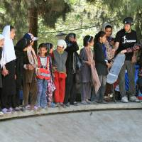 Thrashin': Skateistan founder Oliver Percovich (second from right) teaches young girls in Afghanistan how to skateboard at an old, dried-up water fountain in their community. The film 'Skateistan' focuses on his efforts. | SKATEISTAN