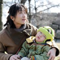A mother holds her son, who suffers from the aftermath of meningitis caused by Haemophilus influenzae type B, in Osaka in 2008. | BLOOMBERG