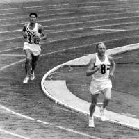 Silver slips away: Great Britain's Basil Heatley heads for the finish line after passing Kokichi Tsuburaya inside Tokyo's National Stadium during the final lap of the marathon on Oct. 21, 1964. | KYODO