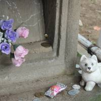 Fatally loyal: Small offerings are left on the gravestone of Hachiko. | DAVEY YOUNG
