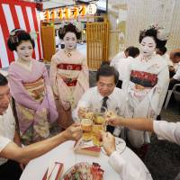 Fine hospitality: Maiko (apprentice geisha) serve customers at a beer garden in Kyoto in true omotenashi style. | KYODO