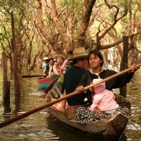 Women of the stilt village in Kompong Phluk on Cambodia's Tonle Sap lake guide tourists through the flooded forest. | MIDORI PAXTON