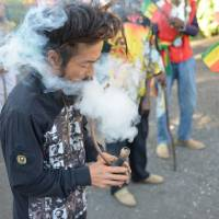 A Japanese Rastafarian named Bongho Jatusy puffs on a ganja pipe outside a museum dedicated to Marley, also in the Jamaican capital. | AP