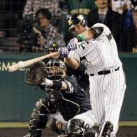 The catalyst: The Tigers' Mauro Gomez hits an RBI double in the fourth inning in Game 1 of the Japan Series on Saturday at Koshien Stadium. Gomez finished with three RBIs in Hanshin's 6-2 victory over the Fukuoka Softbank Hawks. | KYODO
