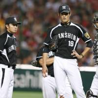 System malfunction: Hanshin starting pitcher Shintaro Fujinami (19) and his teammates assemble during the fourth inning of Tuesday's game. | KYODO