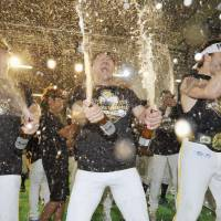 The thrill of it all: (From left) Hawks players Toru Hosokawa, Seiichi Uchikawa and Dennis Sarfate spray beer in the air during the team's Japan Series title jubilations. | KYODO