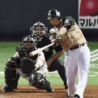 Staying alive: Hokkaido Nippon Ham's Sho Nakata hits a game-tying solo homer in the eighth inning of the Fighters' 6-4 win over the Hawks in Game 5 of the Pacific League Climax Series Final Stage on Sunday. | KYODO