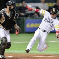 Flying Hawk: Fukuoka Softbank's Kenji Akashi dives home in the fourth inning of the Hawks' 4-1 win over the Fighters in Game 6 of the Pacific League Climax Series Final Stage on Monday. | KYODO
