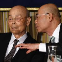 Master sushi chef Jiro Ono (left), owner of the famous sushi restaurant Sukiyabashi Jiro, listens to his son, Yoshikazu Ono, at a press conference held Tuesday at the Foreign Correspondents' Club Japan in Tokyo. | AFP-JIJI