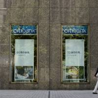 A pedestrian walks past a Citigroup Inc. Citibank branch in Tokyo in August. | BLOOMBERG