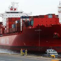 A freighter arrives at Tokyo's international cargo terminal on Tuesday as the government announced a record low first-half current account surplus. | AFP-JIJI