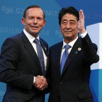 Prime Minister Shinzo Abe is welcomed by Australian Premier Tony Abbott at the Group of 20 leaders' summit on Saturday in Brisbane, Australia. | REUTERS