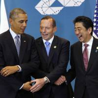 Prime Minister Shinzo Abe, Australian Premier Tony Abbott and U.S. President Barack Obama make a show of unity at their trilateral meeting during the Group of 20 summit in Brisbane, Australia, on Sunday. | REUTERS