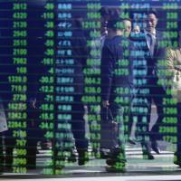 Passers-by are reflected on an electronic stock quotation board outside a brokerage in Tokyo on Monday. The Nikkei stock average tumbled after the economy unexpectedly slipped into recession.   REUTERS