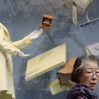 A woman walks past a luxury store in Tokyo's Ginza district on Sunday. The economy shrank an annualized 1.6 percent in the July-September period on the heels of a severe contraction in the previous quarter.   REUTERS