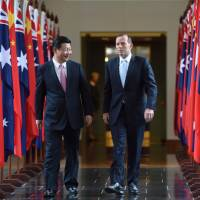 Chinese President Xi Jinping and Australian Prime Minister Tony Abbott walk together as they leave the House of Representatives at Parliament House in Canberra on Monday. | AFP-JIJI