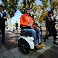 Segway Japan Vice President Dai Akimoto holds a demonstration using the Genny wheelchair, manufactured in Italy, in Tsukuba, Ibaraki Prefecture, on Friday. | AFP