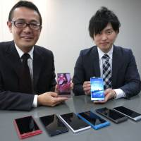 Shigeru Kobayashi (left), general manager of Sharp Corp.'s new business strategic planning department, and Yasuaki Fukuyama, another member of the department, display the electronics maker's latest smartphones on Oct. 28. | KAZUAKI NAGATA