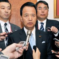 Akira Amari, the Cabinet minister in charge of Trans-Pacific Partnership talks, speaks to reporters in Beijing on Saturday after TPP trade chiefs dropped their goal of striking a broad-based deal by year-end. | KYODO