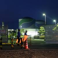 Guards are stationed at the entrance to Kyushu Electric Power Co.'s Sendai nuclear plant in Satsumasendai, Kagoshima Prefecture, on Oct. 26. | BLOOMBERG