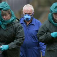 Experts wearing protective suits are seen at a duck farm in the village of Nafferton, in northern England, on Monday. | REUTERS