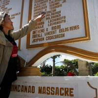 Gloria Teodoro, widow of newspaper reporter Andres Teodoro, touches a marker for victims of the Philippines' Maguindanao massacre in the town of Ampatuan on Friday. | AFP-JIJI