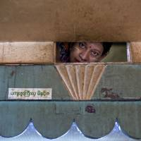 One of Round Namar's daughters peeps into their living room through a window in the attic of their tiny apartment in a building on Yangon's 41st Street on Aug. 25. The family, whose 11 members live in a crowded apartment that has been carved into closet-size rooms, is among the poorest in the building. | AP