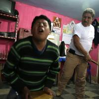 A teenager grimaces in pain as he is lashed by a 'rondero,' a member of a citizen vigilante group known as a 'rondas urbanas,' or urban patrol, in Cajamarca, Peru, in June.. | AP