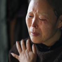 Kim Bok-soon, who underwent 15 operations by a doctor who turned out not to be a specialist in plastic surgery, cries during an interview at her home in Seoul on Oct. 14. | REUTERS