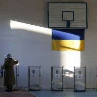 A woman casts her ballot during parliamentary elections at a polling station set up in a school gym in the village of Semyonovka, near Slovyansk in eastern Ukraine, on Oct. 26. | REUTERS