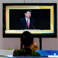A man looks at a screen showing an image of Chinese President Xi Jinping at the media center for the Asia-Pacific Economic Cooperation summit in Beijing on Friday. | AFP-JIJI