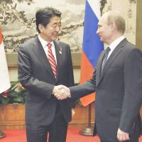Prime Minister Shinzo Abe and Russian President Vladimir Putin shake hands before sitting down for a meeting in Beijing on Sunday. | KYODO