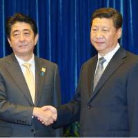 Prime Minister Shinzo Abe shakes hands Monday with Chinese President Xi Jinping before a bilateral summit meeting in Beijing. | KYODO