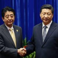 Prime Minister Shinzo Abe shakes hands with Chinese President Xi Jinping before the two held a summit in Beijing on Monday. | AP