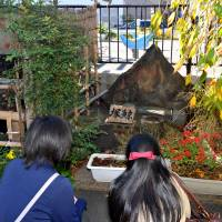 Girls offer silent prayers to the Kujirazuka (whale mound), where the remains of a 16.5-meter whale that beached itself on the coast of Shinagawa on a stormy day in 1798 are buried. | YOSHIAKI MIURA
