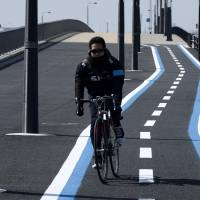 A cyclist uses a bike path in Tokyo's Toyosu district in March. Few such roadside paths exist, but planners are marking out more across the rest of the metropolitan area. | BLOOMBERG