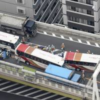 Tour buses involved in an accident are seen on a section of the Metropolitan Expressway in Itabashi Ward, Tokyo, on Saturday morning. Forty-six people, including elementary school children, sustained minor injuries in the accident triggered by a motorcycle changing lanes. | KYODO