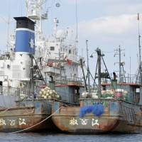 Two Chinese coral fishing boats are anchored next to a Japan Coast Guard patrol ship Tuesday at Kushikino port in Kagoshima Prefecture. The Coast Guard arrested the skippers and raided the boats on suspicion of operating illegally in Japanese waters. | KYODO
