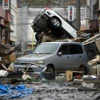 Cars sit abandoned in Ishinomaki, Miyagi Prefecture, on March 15, 2011, four days after the Tohoku region was hit by a massive earthquake and tsunami. | BLOOMBERG