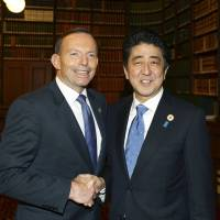 Prime Minister Shinzo Abe is greeted in Brisbane on Saturday by Australian Prime Minister Tony Abbott. | REUTERS