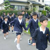 Elementary school students in the town of Hirokawa, Wakayama Prefecture, are led to higher ground during an evacuation drill on Wednesday. | KYODO