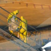 Workers in bioprotective suits transport disinfectant onto an Emirates flight that carried a Guinean woman suspected of having Ebola at Kansai International Airport in Osaka Prefecture on Friday. The woman tested negative for the virus on Saturday.  | KYODO