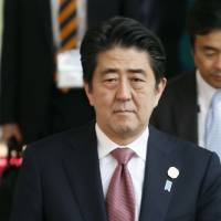 Prime Minister Shinzo Abe leaves a hotel in Brisbane, Australia, on Sunday during his visit there to attend the Group of 20 summit. | KYODO
