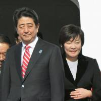 Prime Minister Shinzo Abe and his wife, Akie, arrive at the Beijing International Airport on Sunday for summit meeting of the Asia-Pacific Economic Cooperation forum. Abe is expected to hold talks with Chinese President Xi Jinping on the sidelines of the meeting. | KYODO
