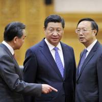 Chinese President Xi Jinping (center), Foreign Minister Wang Yi (left) and State Councillor Yang Jiechi huddle prior to a meeting with Bangladesh President Abdul Hamid at the Great Hall of the People in Beijing on Saturday. | REUTERS