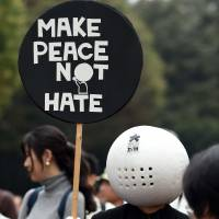 An anti-racism protester holds up a placard during a rally in Shinjuku Ward, Tokyo, on Sunday. | AFP-JIJI