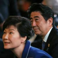 Prime Minister Shinzo Abe and South Korean President Park Geun-hye attend an event at the Group of 20 summit in Brisbane, Australia, on Nov. 15. Both nations face controversies over how textbooks depict contentious historical events. | REUTERS