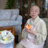 Jito Sasaki, a nun in Nara Prefecture, folds a piece of origami paper at a hospice in Tokyo, where she volunteers several days a month. | KYODO