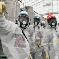 Trade and industry minister Yoichi Miyazawa (right) inspects the ALPS water-treatment facility at the crippled Fukushima No. 1 nuclear plant on Saturday during his first visit to the area since taking the post last month. | POOL
