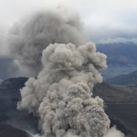 An aerial photo taken Wednesday shows volcanic smoke billowing from Mount Aso in southwestern Japan. A local observatory said it has seen no sign of intensifying volcanic activity. | KYODO